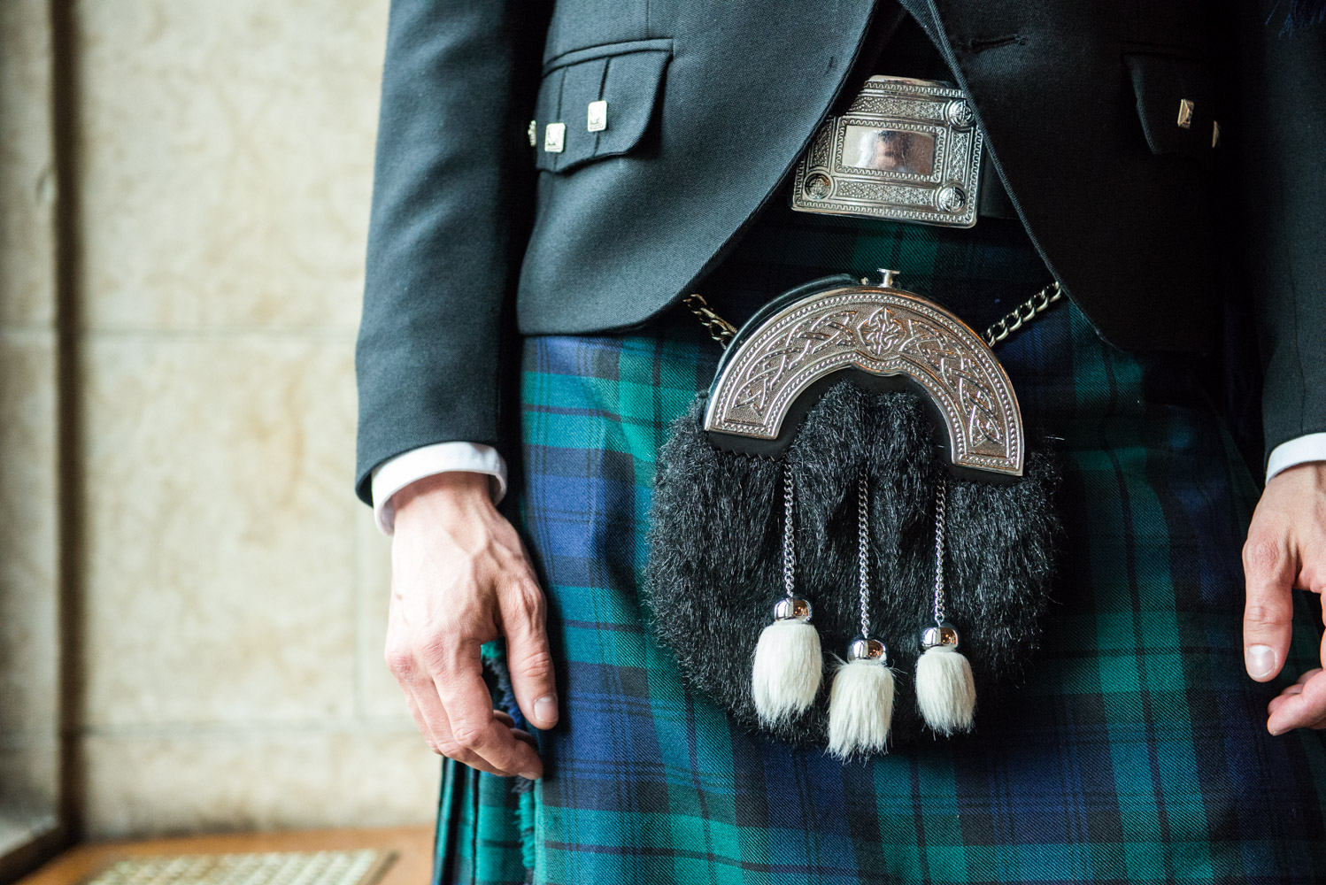 A man wearing a belt and sporran with full Highland dress.